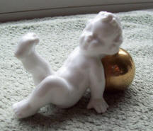 Putti reclining on gold ball